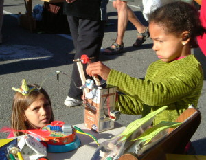 Young girls with solar crane at Saturday market